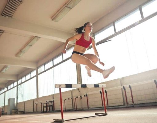 woman jumping over obstacle